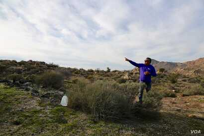 Enrique Morones, founder and director of the human rights organization Border Angels, leaves a bottle of water for dehydrated migrants in the Southern California desert. (R. Taylor/VOA)