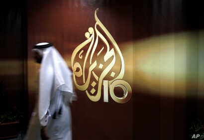 FILE - A Qatari employee of Al Jazeera Arabic language TV news channel walks past the logo of Al Jazeera in Doha, Qatar,