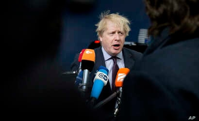 British Foreign Secretary Boris Johnson speaks with the media as he arrives for a meeting of EU foreign ministers at the Europa building in Brussels on Monday, March 19, 2018.