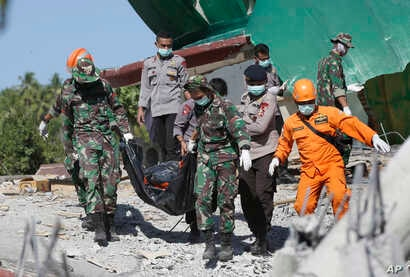 Rescuers carry the body of an earthquake victim recovered from debris of a collapsed mosque in North Lombok, Indonesia, Aug. 7, 2018.