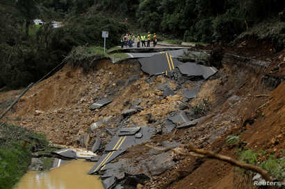 People look at a highway, that connects with the south of the country, collapsed by Storm Nate in Casa Mata, Costa Rica, Oct. 6, 2017.