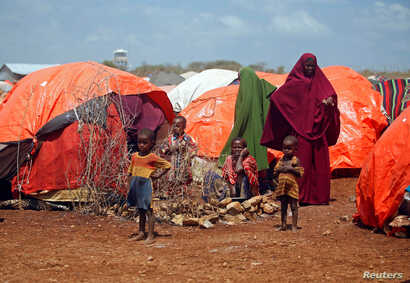 An internally displaced Somali family is seen outside their makeshift shelter at a camp after fleeing from drought stricken regions in Baidoa, west of Somalia's capital Mogadishu, April 9, 2017.