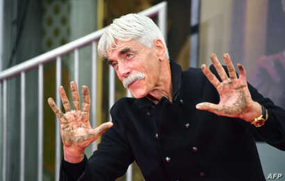 Actor Sam Elliott displays his hands after placing them in the block of cement during his Hand and Footprints ceremony in Hollywood, California, Jan. 7, 2019.