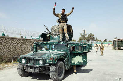 An Afghan soldier raises his hands as a victory sign, in Kunduz city, Oct. 2, 2015.