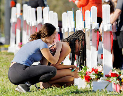 A senior at Marjory Stoneman Douglas High School weeps in front of a cross and Star of David for shooting victim Meadow Pollack while a fellow classmate consoles her at a memorial by the school in Parkland, Florida, U.S. February 18, 2018.