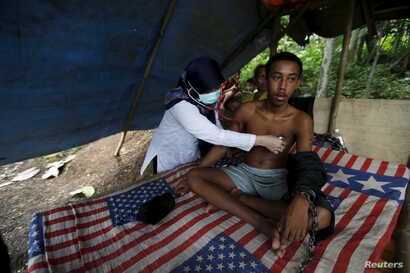 A doctor checks the health of Deden, a teenager whose father says suffers from mental illness and lives chained to a tree next to a rice paddy near his home in Longkewang village in Serang, Banten province, Indonesia, March 23, 2016.
