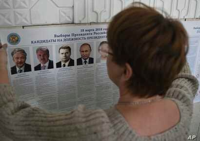 A polling station official hangs a list of candidates for the 2018 Russian presidential election, during preparations at a polling station in Simferopol, Crimea, March 17, 2018. Russian voters, observers and eight presidential candidates are gearing ...