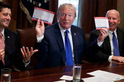 President Donald Trump holds an example of what a new tax form may look like during a meeting on tax policy with Republican lawmakers including House Speaker Paul Ryan of Wis., and Chairman of the House Ways and Means Committee Rep. Kevin Brady, R-Te