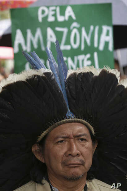"""Indigenous leader Kreta Kaingang stands in front of  a sign that reads in Portuguese """"For the Amazon. Urgent!""""  during a protest against right-wing presidential candidate Jair Bolsonaro, in front of the Ministry of Environment in Brasilia, Brazil, Oc..."""