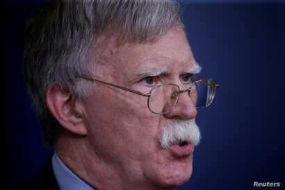 "FILE - U.S. national security adviser John Bolton answers questions from reporters after announcing that the U.S. will withdraw from the Vienna protocol and the 1955 ""Treaty of Amity"" with Iran, during a news conference in the White House briefing ro..."