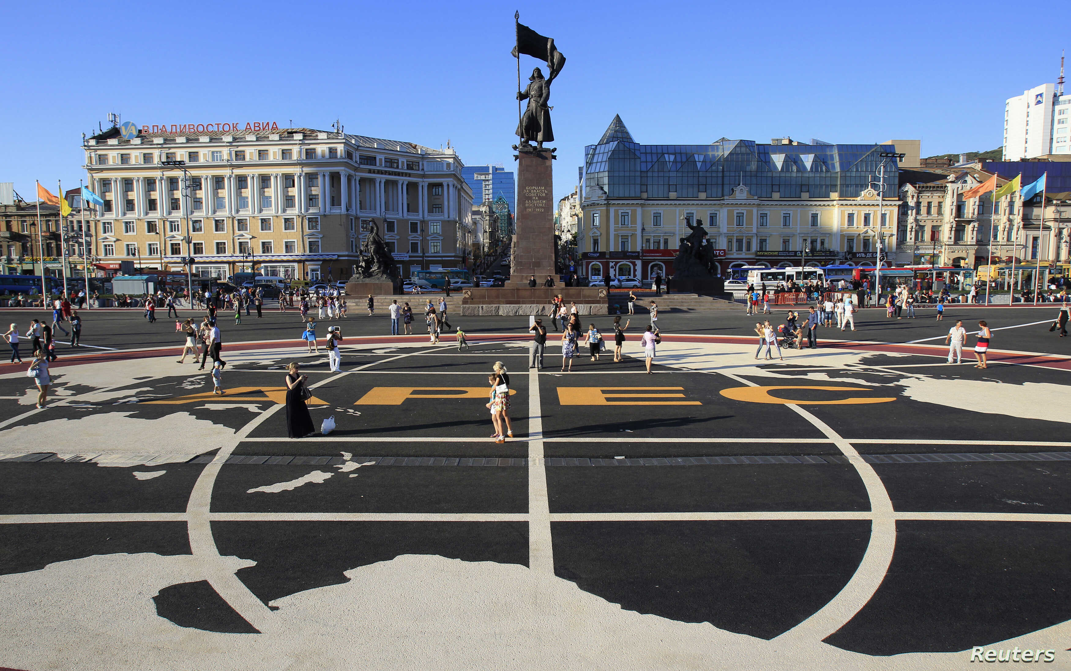 People walk over a tarmac with the Asia-Pacific Economic Cooperation (APEC) logo printed on it, in a central square of Vladivostok, Russia, September 6, 2012.