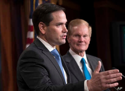 Sen. Marco Rubio, R-Fla., joined at right by Sen. Bill Nelson, D-Fla., holds a news conference to unveil his plan to address gun violence with legislation on restraining orders, at the Capitol in Washington, March 7, 2018.