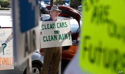 Paul Gipe protests before the first of three public hearings on the Trump administration's proposal to roll back car-mileage standards in a region with some of the nation's worst air pollution, Sept. 24, 2018, in Fresno, California.