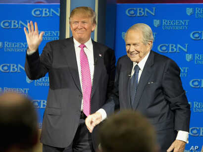 On Feb. 24, 2016, Republican presidential candidate, Donald Trump, accompanied by Rev. Pat Robertson, waves as he arrives for an appearance at Regent University in Virginia Beach, Virginia.