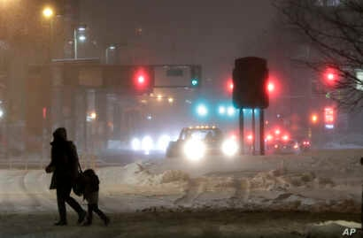 A woman and a child cross a snow-covered street during a snowstorm, Wednesday, March 21, 2018, in Jersey City, N.J. A spring nor'easter targeted the Northeast on Wednesday with strong winds and a foot or more of snow expected in some parts of the reg