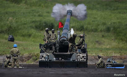 FILE - Japanese Ground Self-Defense Force soldiers fire a self-propelled howitzer during annual exercises near Mount Fuji at Higashifuji training field in Gotemba, west of Tokyo, Aug. 19, 2014.