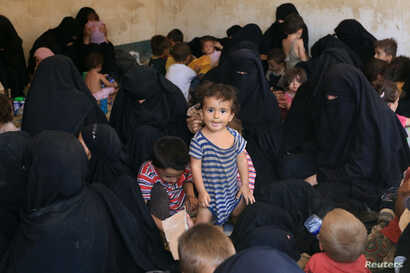 Families and relatives of Islamic State militants are seen after they surrendered themselves to the Kurdish Peshmerga forces in al-Ayadiya, northwest of Tal Afar, Iraq, Aug. 30, 2017.
