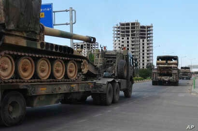 FILE - A convoy of Turkish military trucks carrying tanks destined for Syria, moves near the town of Kilis, Turkey, Sept. 14, 2018.