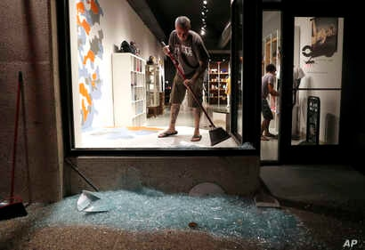 Scott McRoberts helps clean up broken glass after a violent crowd broke windows of many businesses after clashing with police, Sept. 16, 2017, in University City, Mo. Earlier, protesters marched peacefully in response to a not guilty verdict in the t...