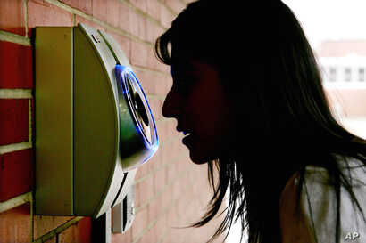 FILE - A woman uses an iris scanner to enter an elementary school in Freehold, N.J. Those who choose to register with the system can use the iris-scanning camera to unlock doors automatically. The African region of Somaliland has become the first to ...