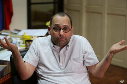 """FILE - Jose Luis Martin """"Chito"""" Gascon, chair of the Commission on Human Rights (CHR) gestures during an interview in Quezon City, north of Manila, Philippines, Sept. 9, 2016."""