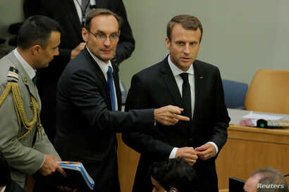 French President Emmanuel Macron, right, arrives for a high-level meeting to discuss the current situation in Libya during the 72nd U.N. General Assembly at U.N. headquarters in New York, Sept. 20, 2017.