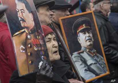 FILE - Communists carry portraits of former Soviet leader Joseph Stalin as they march along Kremlin Towers during a May Day rally in Moscow, May 1, 2015.