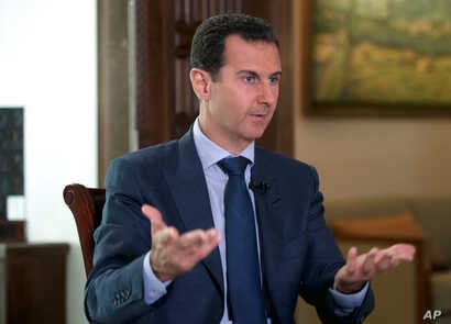 In this Wednesday, Sept. 21, 2016 photo released by the Syrian Presidency, Syrian President Bashar Assad speaks to The Associated Press at the presidential palace in Damascus, Syria.
