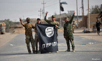 Shi'ite Popular Mobilization Forces (PMF) fighters remove an Islamic State flag after liberating the city of Al-Qaim, Iraq Nov. 3, 2017.
