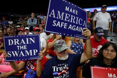 Supporters hold signs as President Donald Trump speaks during a rally Aug. 21, 2018, in Charleston, W.Va.