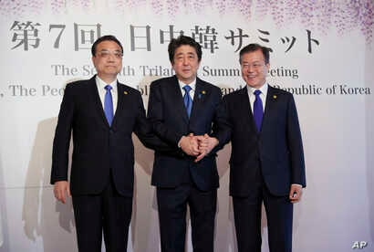 Chinese Premier Li Keqiang, left, Japanese Prime Minister Shinzo Abe, center, and South Korean President Moon Jae-in, right, pose for photographers before their summit in Tokyo, May 9, 2018.