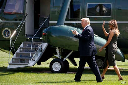 President Donald Trump gestures to onlookers as he walks with first lady Melania Trump to board Marine One on the South Lawn of the White House, Sept. 8, 2017.