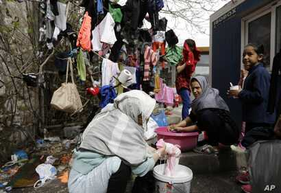 Afghan women wash and dry their clothes in Piraeus, near Athens, March 8, 2016. European Union leaders said they reached the outlines for a possible deal with Ankara to return thousands of migrants to Turkey early Tuesday.