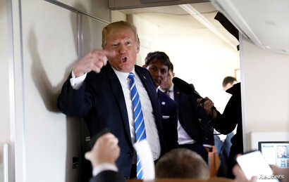 U.S. President Donald Trump speaks to reporters aboard Air Force One after visiting White Sulphur Springs, W.Va., April 5, 2018.