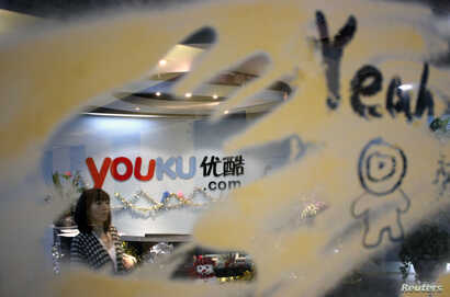 FILE - An employee is seen through a glass wall as she walks past the logo of Youku.com above the reception desk at the company's headquarters in Beijing, Dec. 9, 2010.