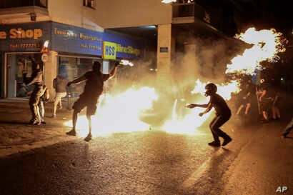 Protesters throw petrol bombs at policemen during an anti-fascist rally, commemorating the killing of Greek rap singer Pavlos Fyssas, in Athens, Sept. 16, 2017.