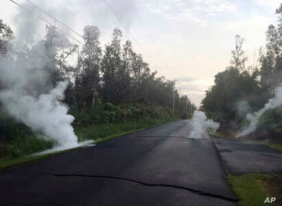 Steam rises from cracks in the road shortly before a fissure opened up on Kaupili Street in the Leilani Estates subdivision, May 4, 2018, in Pahoa, Hawaii, in this image released by the U.S. Geological Survey.