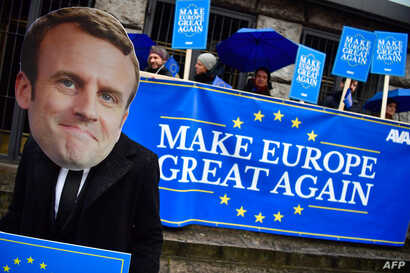 "Activists of the Avaaz civic organization wear a mask of French President Emmanuel Macron and hold up posters and a banner reading ""Make Europe Great Again"" as they demonstrate in Berlin in front of the venue where are meeting the leaders of Germany'..."