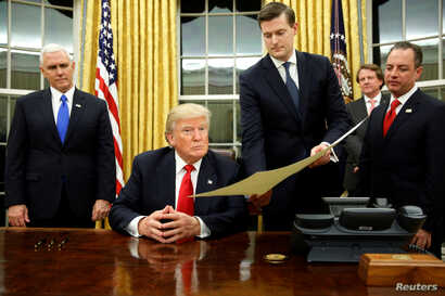 FILE - White House Staff Secretary Rob Porter (2nd-R) gives U.S. President Donald Trump, flanked by Vice President Mike Pence (L) and Chief of Staff Reince Priebus (R) the document to confirm Secretary of Defense James Mattis, Trump's first signing i...