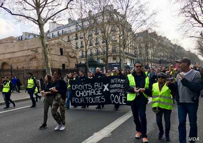 """Yellow vest"" protesters in Paris carry a banner calling for rights for the unemployed. (L. Bryant/VOA)"