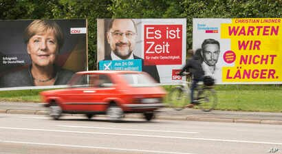 Election posters showing German Chancellor Angela Merkel, CDU, social democrat challenger Martin Schulz, SPD, center, and Free Democratic Party, FDP, federal chairman Christian Lindner, right, stand at a street in Erfurt, central Germany, Sept. 15, 2...