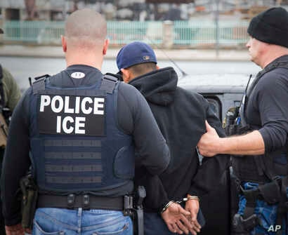 FILE -  U.S. Immigration and Customs Enforcement (ICE) agents arrest foreign nationals, Feb. 7, 2017, in Los Angeles.  In New York on Tuesday a lawyer threatened to call ICE because he heard cafe workers speaking Spanish.