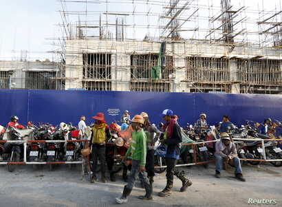 FILE - Laborers rest in front of a construction site of the HongKong Land in Phnom Penh, Cambodia, Oct. 19, 2015.  High-rise apartments are springing up across Cambodia's capital, part of a property boom led by expat demand, while developers are also...
