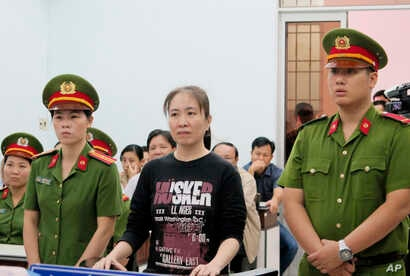 FILE - Nguyen Ngoc Nhu Quynh, center, a prominent Vietnamese blogger, stands trial in the south-central province of Khanh Hoa, Vietnam.
