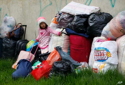 A young Venezuelan migrant waits next to her family's belongings before leaving a makeshift migrant settlement near the main bus terminal in Bogota, Colombia, Nov. 13, 2018.