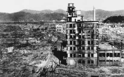 FILE - In this Aug. 8, 1945, photo, survivors walk past one of the few buildings still standing two days after the United States dropped an atomic bomb on Hiroshima, Japan, two days earlier.
