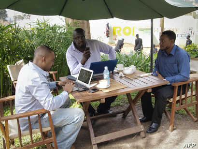 FILE - Men work on their laptops at the Endiro Cade in Kampala.