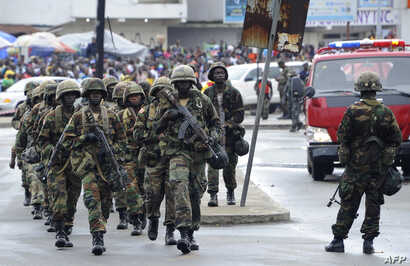 Liberian army soldiers walk on the Monrovia bridge during a training excercise as the United Nations Mission in Liberia forces (UNMIL) finally hands back security to Liberia's military and police, in Monrovia on June 24, 2016.