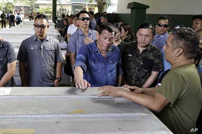 Philippine President Rodrigo Duterte, center, touches one the caskets of some of the victims of the bombings, Jan. 26, 2018, of a Roman Catholic Cathedral on Jolo, Sulu province in southern Philippines, during his visit Monday.