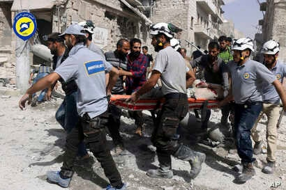 FILE - In this Wednesday, Sept. 21, 2016, file photo, provided by the Syrian Civil Defense White Helmets, rescue crews work the site of airstrikes in the al-Sakhour neighborhood of the rebel-held part of eastern Aleppo, Syria.